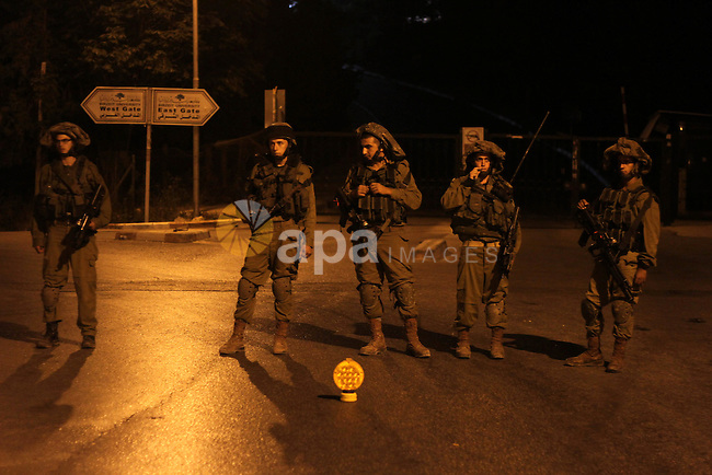 Israeli soldiers patrol at Birzeit University, on the outskirts of the city of Ramallah in the West Bank during an operation on June 19, 2014 as Israeli forces broadened the search for three teenagers believed kidnapped by militants and imposed a tight closure of the town. Israeli Prime Minister Benjamin Netanyahu demanded Palestinian president Mahmud Abbas's help in securing the release of three kidnapped teenagers, as the army launched a massive crackdown on Islamist movement Hamas. Photo by Issam Rimawi