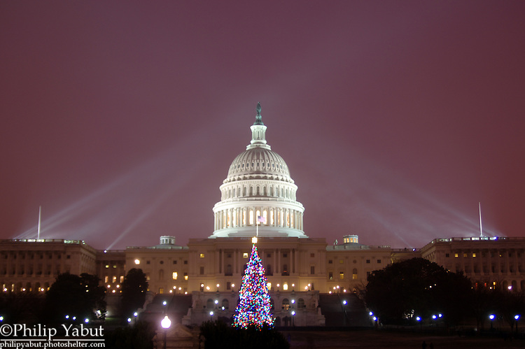 Falling snow highlights the Capitol dome's illuminating spotlights.