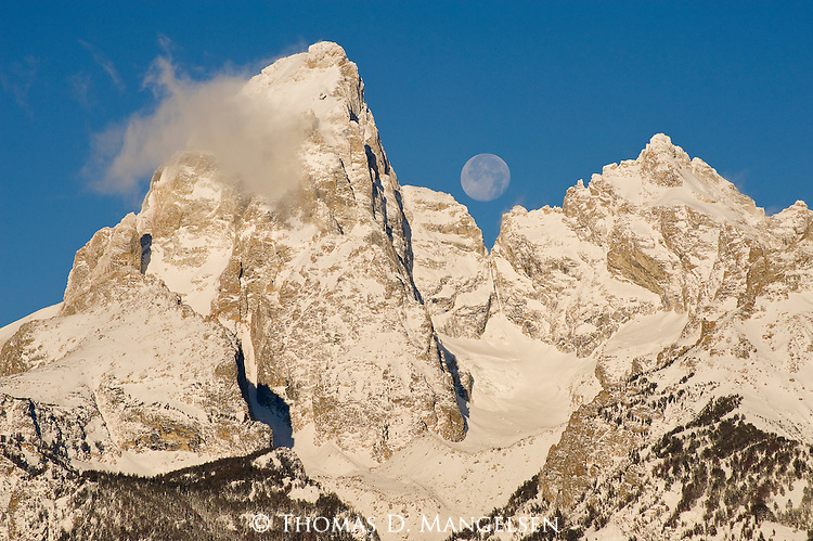 The full moon shows between the Grand Teton and Mount Owen in Northwest Wyoming.