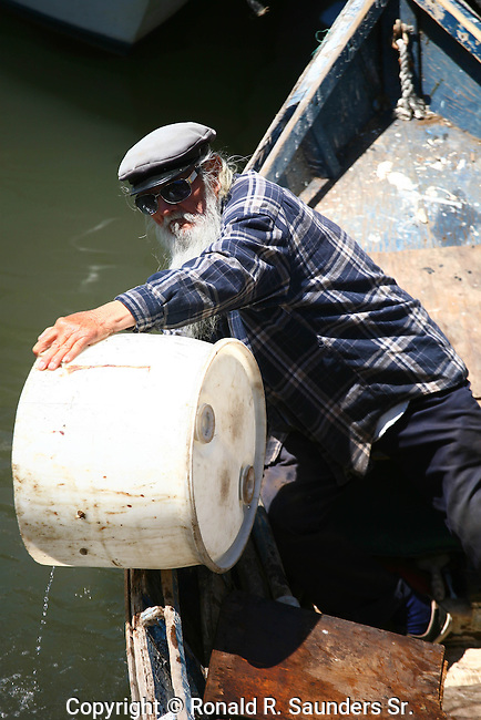 Whiskered old man in panga boat empties water into harbor.<br /> (1)