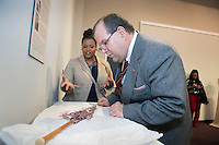 Junior human sciences/fashion design and merchandising major Fleshia D. Gillon of Amory and MSU School of Human Sciences Professor and Director Michael Newman examine a violet silk umbrella from the MSU Historic Costume and Textiles Collection. Part of the university's &quot;Silk Unraveled: A Revealing Look at the History and Use of Silk Fabric&quot; exhibit on display through March 29 at the Cullis Wade Depot Art Gallery, the umbrella dates to the late 19th and early 20th centuries and is among featured objects designed to give visitors a better appreciation of silk&rsquo;s importance from Old World origins to the modern age.<br />