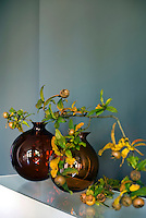 On an open shelf in this living room autumnal medlar branches have been arranged in two brown glass vases designed by Anna Torfs