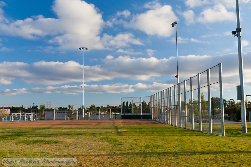 An overview of the baseball field at Stanton Central Park, with puffy white clouds in a blue sky.