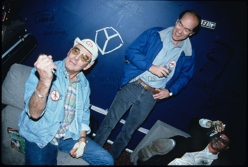 Hunter S. Thompson, Aspen Mayor John Bennett, and local columnist Dan Dunn at a voter registration party in Aspen, CO on 11/7/95. Thompson is spraying a permanent dye ink throughout the room, and Dunn has taken face full. Thompson was later arrested that night for driving while alcohol impaired. © Michael Brands. 970-379-1885.