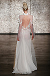 Model walks runway in a long sleeve beaded gown with collar and open back and point D'esprit skirt, from Inbal Dror Fall 2018 bridal collection on October 5, 2017; during New York Bridal Fashion Week.