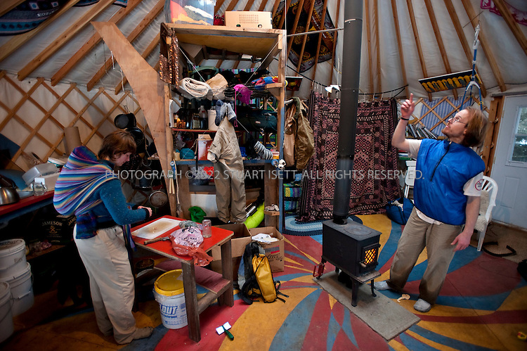 12/11/2009--Seldovia, Alaska, USA..Erin McKittrick (left), with her son, Katmai, strapped to her back, prepares lunch in their yurt in Seldovia, Alaska while her husband, Bretwood Higman looks at the ceiling...The yurt is made by Nomad Shelter in Homer, Alaska, and cost about $14,000.  Bretwood Higman ('Hig'), 33 and Erin McKittrick, 30, built it in November, 2008 on land owned by Hig's mother in Seldovia. The yurt is 24' in diameter, the ceiling is over 12' in the middle, 7' around the edge. It has no running water but does have electricity and internet access...McKittrick grew up in Seattle and met Higman, from Seldovia, at Carleton College in 2001.  In June 2007, the couple left Seattle for the Aleutian Islands, traveling 4000 miles solely by human power through some of the most rugged terrain in the world; their adventure has recently been published in a book written by McKittrick with Hig's photographs titled, 'A Long Trek Home: 4,000 Miles by Boot, Raft, and Ski'...Together, the couple also run a small environmental non-profit, Ground Truth Trekking, which uses trekking to explore the complexities of natural resource issues.  The couple lives with their 10 month old son son, Katmai, in Seldovia, Alaska, a 300 person village just off the end of the road system...©2009 Stuart Isett. All rights reserved.