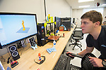 Mechanical engineering sophomore Blake Horner show off some samples of a statue, the brown one in the center, that were printed on one of the CME's 3D printers.  Photo by Kevin Bain/University Communications Photography