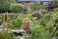 Artist's backyard cottage garden with pond. House in background. Sally Robertson Garden.
