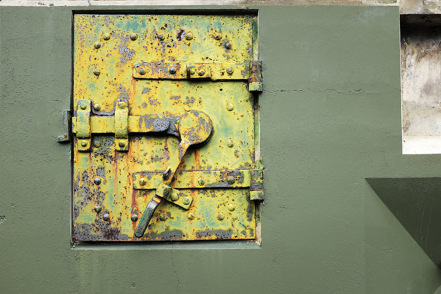 Rusty yellow steel door on wall of green concrete bunker, Artillery Hill, Fort Worden State Park, Port Townsend, Washington, USA