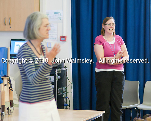 Head Teacher talking (with BSL signing in the background) to parents and pupils, Special Centre for hearing impaired children, state primary school.