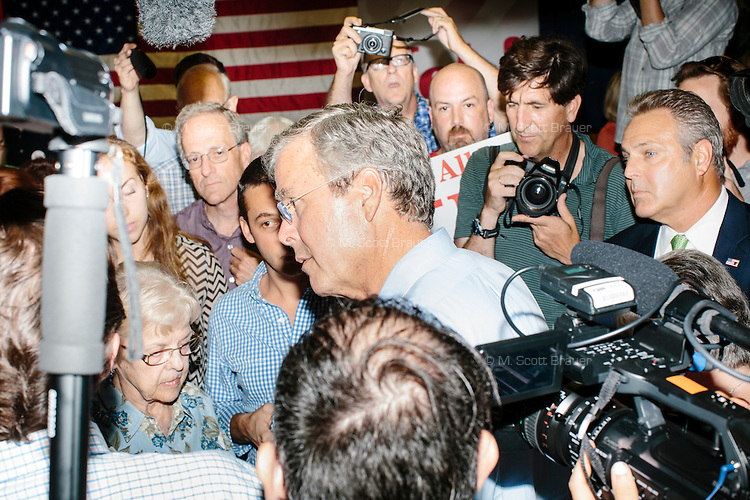 Media surround Republican presidential candidate and former Florida governor Jeb Bush as he greets people and signs autographs after a town hall campaign event at the Hudson VFW in Hudson, New Hampshire.