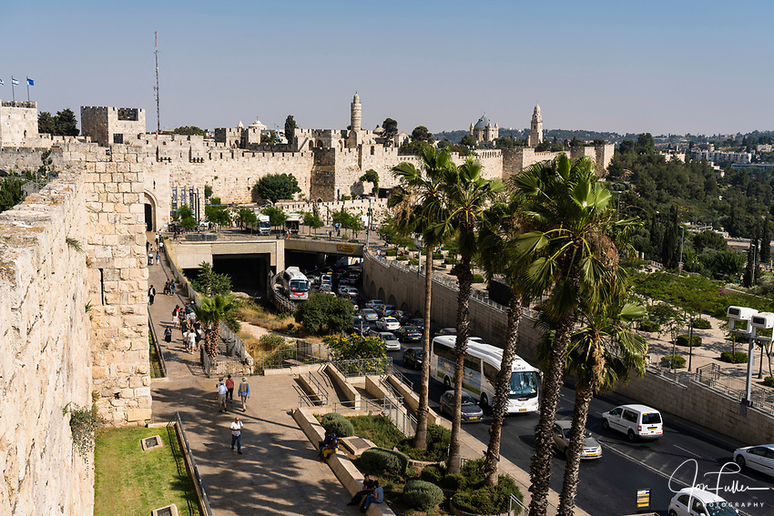 The city wall of Jerusalem near the Jaffa Gate with the minaret of the Tower of David or the Citadel in the center.  At right is the church and bell tower of the Dormition Abbey on Mount Zion, outside the walls.  The Old City of Jerusalem and its Walls is a UNESCO World Heritage Site.