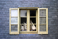 Slate-sided home and old glass in shutters frames an old ship facing out to the sea.