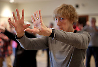 NWA Democrat-Gazette/DAVID GOTTSCHALK Claudette Lunsford participates Friday, January 5, 2018, in a Tai Chi class lead by Master Paul Davis inside the Walker Community Room at the Fayetteville Public Library. The classes are offered on Friday's during the month of January from 9:30 a.m. to 11:00 a.m.. Tai Chi focuses on physical and mental balance, incorporating slow movement, deep breathing, and a relaxed posture.