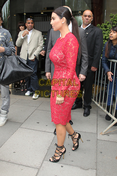 Kim Kardashian  .Leaving her hotel, London, England..March 18th, 2012.full length red pink lace dress strappy black sandals side profile ponytail.CAP/HIL.©John Hillcoat/Capital Pictures.