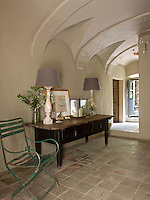 A pair of antique lamps with muted mauve shades on a large wooden console table in the ground floor vaulted entrance hall