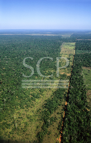 Amazon, Brazil. Aerial view of partly deforested land showing long straight road with deforestation beside it.