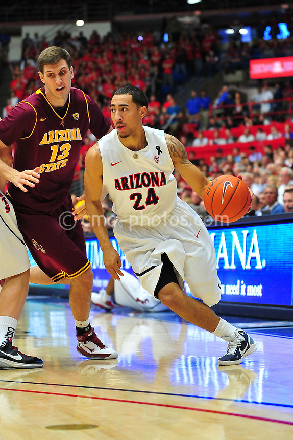 Jan 15, 2011; Tucson, AZ, USA; Arizona Wildcats guard Brendon Lavender (24) dribbles the ball past Arizona State Sun Devils center Jordan Bachynski (13) in the 2nd half of a game at the McKale Center.  The Wildcats won the game 80-69.