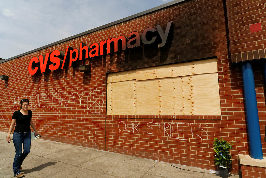 A woman walks past a pharmacy that was looted that was looted during the violence in West Baltimore. April 30, 2015. to go with Nick O'Malley story.  photo by Trevor Collens