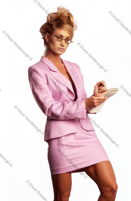 Photo of a secretarty in a pink skirt suit looking at the boss with a pad and pen in her hand.