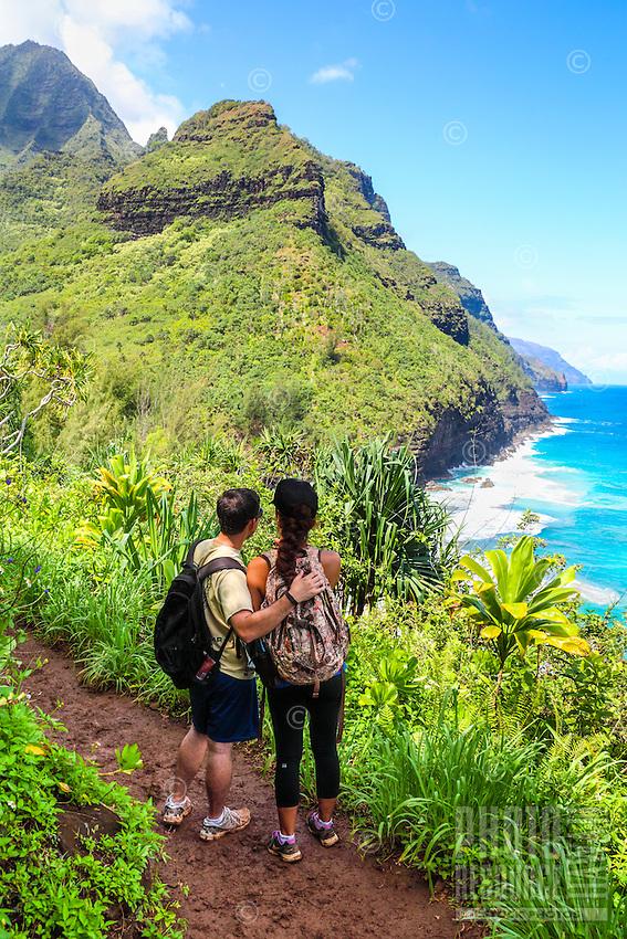 Hikers embrace as they look at the Napali (or Na Pali) coastline from the Kalalau Trail near Hanakapi'ai Beach, North Kaua'i.