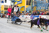 Jessie Royer and team leave the ceremonial start line with an Iditarider at 4th Avenue and D street in downtown Anchorage, Alaska during the 2015 Iditarod race. Photo by Jim Kohl/IditarodPhotos.com