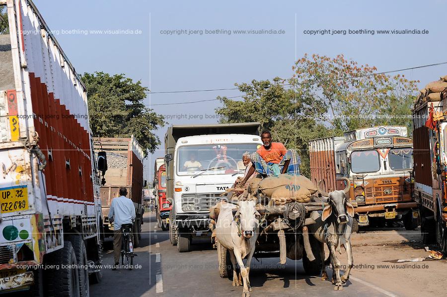 INDIA, Uttar Pradesh, Banda, heavy traffic with Tata trucks and bullock cart