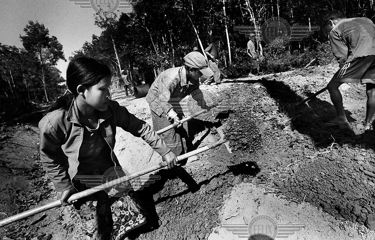 Villagers building a road to open up their area, which was previously cut off from the outside world. Each village in the area is responsible for building a stretch of the road. Before its construction began, a Mines Advisory Group (MAG) team cleared unexploded ordnance (UXO) from the route..Decades on, Laos is still living with the effects of the Vietnam war. Millions of bombs were dropped by US aircraft in Laos in an attempt to destroy the supply lines of North Vietnamese forces. Many remain deadly, with frequent accidents involving unexploded ordnance (UXO). At the same time, ingenuity has transformed the detritus of war, adapting it for multitudinous everyday uses.