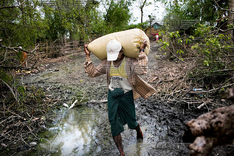Four weeks after Cyclone Nargis, a man carries a bag of clothes handed out by a small group of Burmese aid workers and donated by private donors. Acts of private altruism such as this have been common in reaction to the ruling junta's lack of an organised response. Cyclone Nargis hit Burma on 02/05/2008....