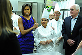 Washington, DC - February 22, 2009 -- First Lady Michelle Obama greets White House Head Chef Cristeta Comerford as she talks to culinary students from L'Academie de Cuisine during a preview for the Governors' Dinner in the White House kitchen in Washington on Sunday, February 22, 2009. .Credit: Kevin Dietsch - Pool via CNP