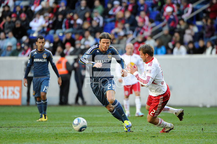 David Beckham (23) of the Los Angeles Galaxy is defended by Teemu Tainio (2) of the New York Red Bulls during the 1st leg of the Major League Soccer (MLS) Western Conference Semifinals at Red Bull Arena in Harrison, NJ, on October 30, 2011.