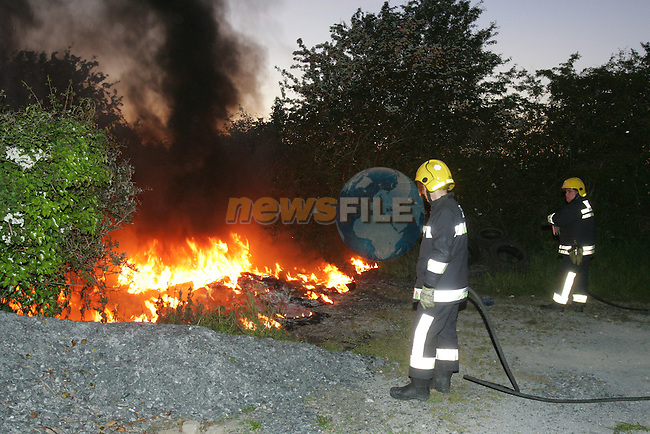 Members of the Drogheda Fires service tackle a tyre fire set by children on a lane leading to a local Rugby club. About 100 tyres were set on fire on a beautiful blue sky evening sending a black cloud over the town of Drogheda. Fire service personel had to cut the locks to gain access..Photo: Fran Caffrey/ Newsfile.