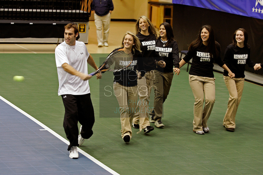 Robby Ginepri is handicapped in a for-fun shootout by Kennesaw State University tennis team members Lindsey Whalen, Diana Georgescu, Mercedes Cobos, Paula Takara, Jeni Thomas and others before The FedEx Shootout Atlanta at Kennesaw State University on Saturday, Dec. 9, 2006.