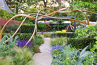 Garden sculpture artwork with gazebo, ornamental grass perennials, spiky plants, mix of textures. Steam bent oak wood. Design by Andy Sturgeon for Cancer Research, 2007 Chelsea Flower Show Gold Medal winner.