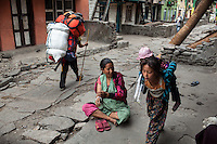 A porter carrying a load from a trekking group walks past a family in front of their home. Shyafru, Nepal 02 May 2013
