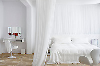 A spacious white bedroom with a double bed enclosed by a sheer curtian. An Eero Saarinen Tulip chair is placed in front of a dressing table shelf.