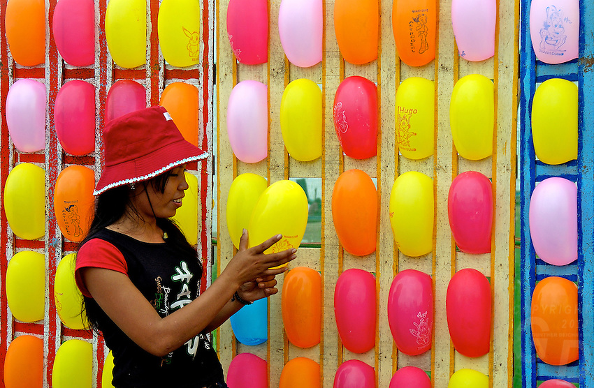 During the annual boat races in Phnom Penh Cambodia, festivities are held, like  trowing darts at these colorful balloons, for a small prize.The poor peoples entertainment