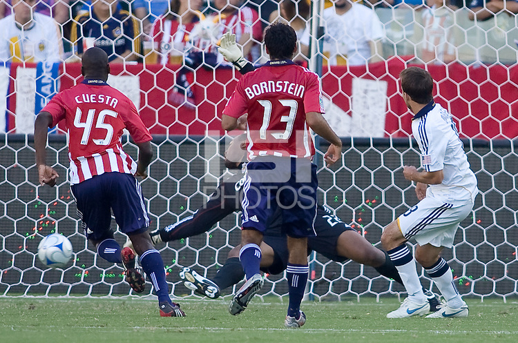 LA Galaxy midfielder Mike Magee scores a goal past Chivas USA goalkeeper Zach Thornton and field players Yamith Cuesta (l) and Jonathan Bornstein (r). The LA Galaxy and Chivas USA played to 2-2 draw during a MLS Western Conference playoff game at Home Depot Center stadium in Carson, California on Sunday November 1, 2009...