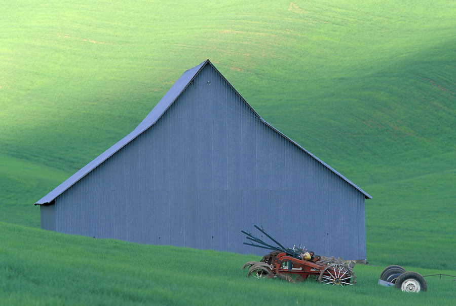 Barn and farming equipment rest in wheat field, Palouse area, Washington.