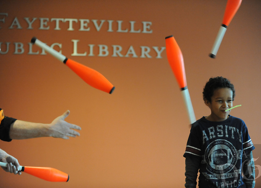 NWA Democrat-Gazette/ANDY SHUPE - Michael Shoffit, 7, of Farmington laughs as Galen Harp (left) and Ellen Winters of The Institute of Jugglology in Fayetteville perform with his assistance during a show Saturday, March 21, 2015, at the Fayetteville Public Library. Shoffit held a straw in his mouth which Harp struck with a juggling club.