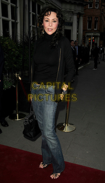 MARIE HELVIN.The Cadogan Hotel's 120th anniversary party, 75 Sloane St., London, England..April 15th, 2008.full length black top turtleneck polo neck bag purse jeans denim jacket .CAP/CAN.©Can Nguyen/Capital Pictures.