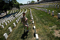 A boy scout puts an American flag into a soldier grave before the memorial day commemorations at the Cypress Hill cemetery in New York City, United States 05/23/2015. Kena Betancur/VIEWpress