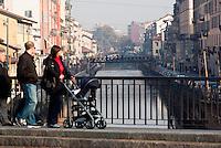 Milano, una famiglia con passeggino la domenica al Naviglio Grande --- Milan, a family with stroller on Sunday at the Naviglio Grande canal