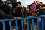 Foreign workers crowd up against the gate on the Libyan side of the border near Ben Guerdane, Tunisia, Friday, Feb. 25, 2011. Thousands crossed the border into Tunisia, fleeing the violence of an uprising in Libya. Opposition forces reportedly have control of much of the country, but Col. Muammar Qaddafi still controls the capital Tripoli.