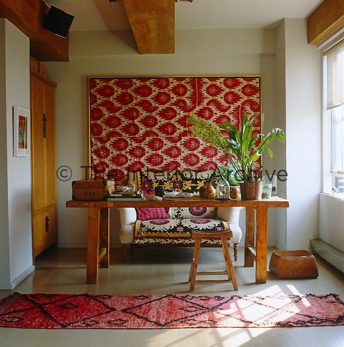 A large framed antique Ikat hangs on the wall in the open-plan home office with a French farmhouse table used as a desk