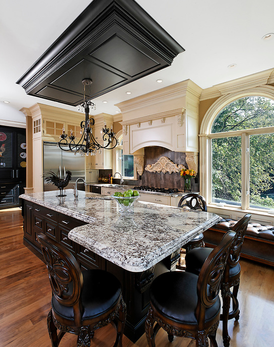 Traditional kitchen with black & white marble island, dark wood and cream painted cabinets.