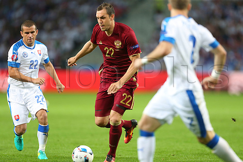 15.06.2016. Lille, France. UEFA Euro 2016 Group B soccer match Russia and Slovakia at Stade Pierre Mauroy in Lille Metropole, France, 15 June 2016.  Viktor Pecovsky (Slo) challenges the break from Artem Dzyuba (Rus)