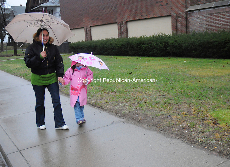 TORRINGTON, CT-30 MARCH 2010-033010IP02-    Marina Estrada (left) and Nicole Arias, of Torrington, use umbrellas as they walk down N. Elm St. in Torrington during heavy rains on Tuesday. <br /> Irena Pastorello Republican-American