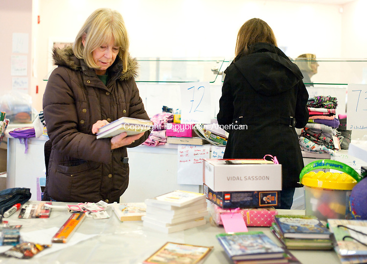 Southbury, CT- 09 December 2015-120915CM01-  Shirley Michaels of Southbury organizes books in Southbury on Wednesday.   Volunteers with the Southbury Needy Fund were bagging donated gifts for children this Christmas.      Christopher Massa Republican-American