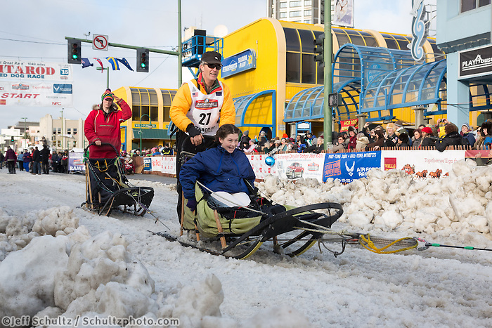 Linwood Fiedler and team leave the ceremonial start line with an Iditarider at 4th Avenue and D street in downtown Anchorage, Alaska during the 2015 Iditarod race. Photo by Jim Kohl/IditarodPhotos.com